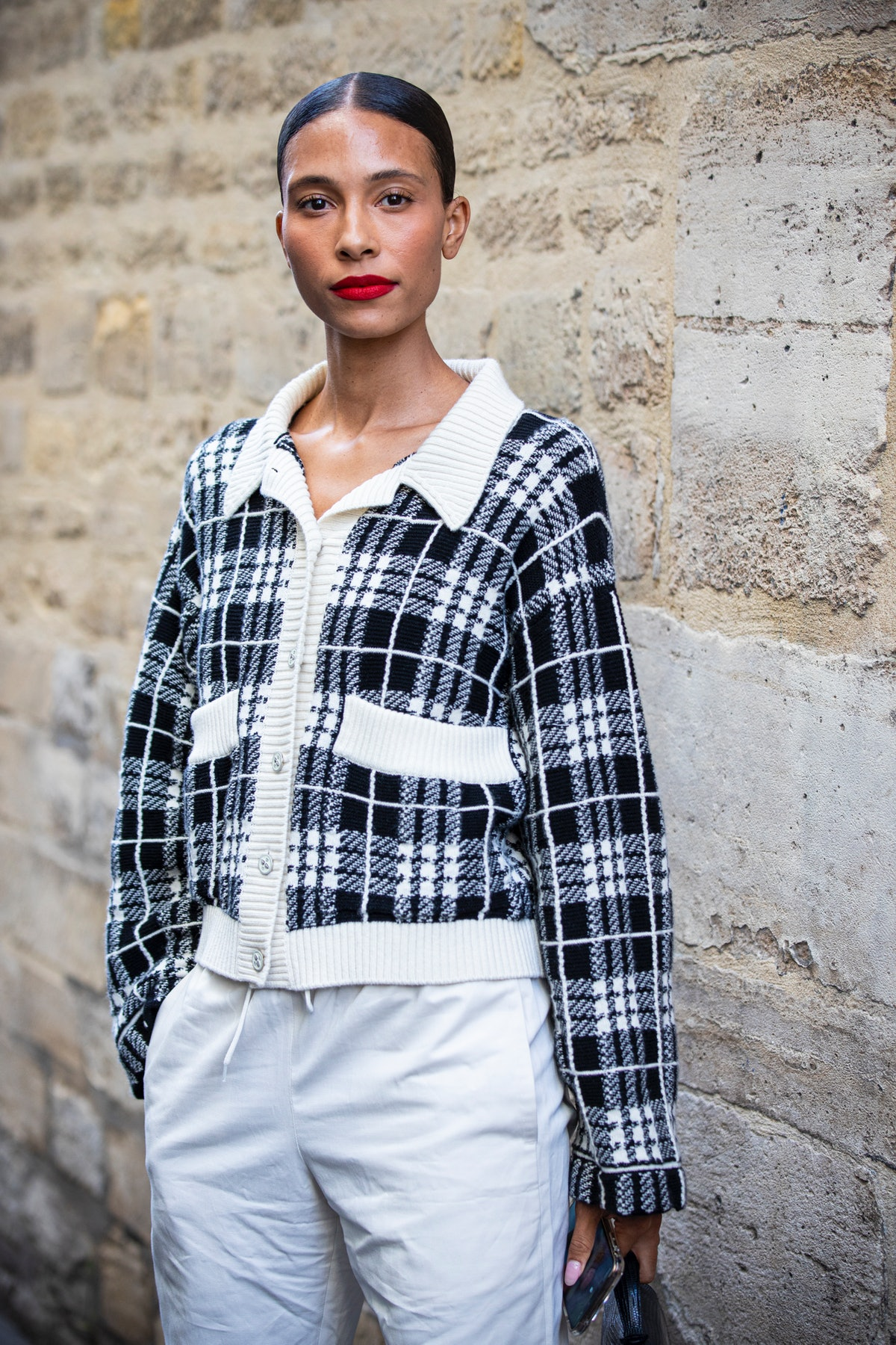 PARIS, FRANCE - SEPTEMBER 30: A guest, wearing a black and white checked cardigan and white pants, i...