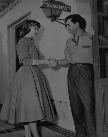 American actor Jack Webb (1920 - 1982) welcomes actress Ann Robinson onto the set of the film 'Dragn...