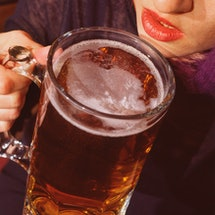 A woman drinks a massive beer alone at a bar. Going to bars alone can be an exercise in self-affirma...