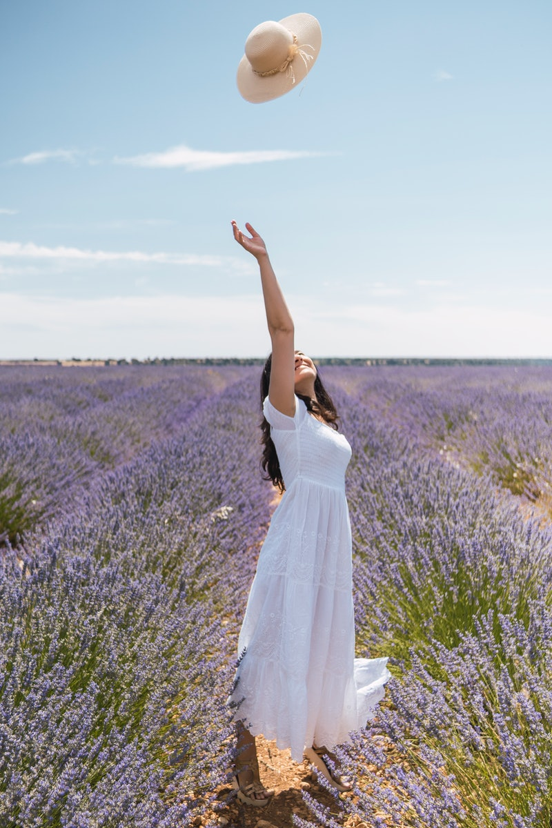 A woman in a lavender field tosses her hat in the air, free from the tyranny of social media. Here's...