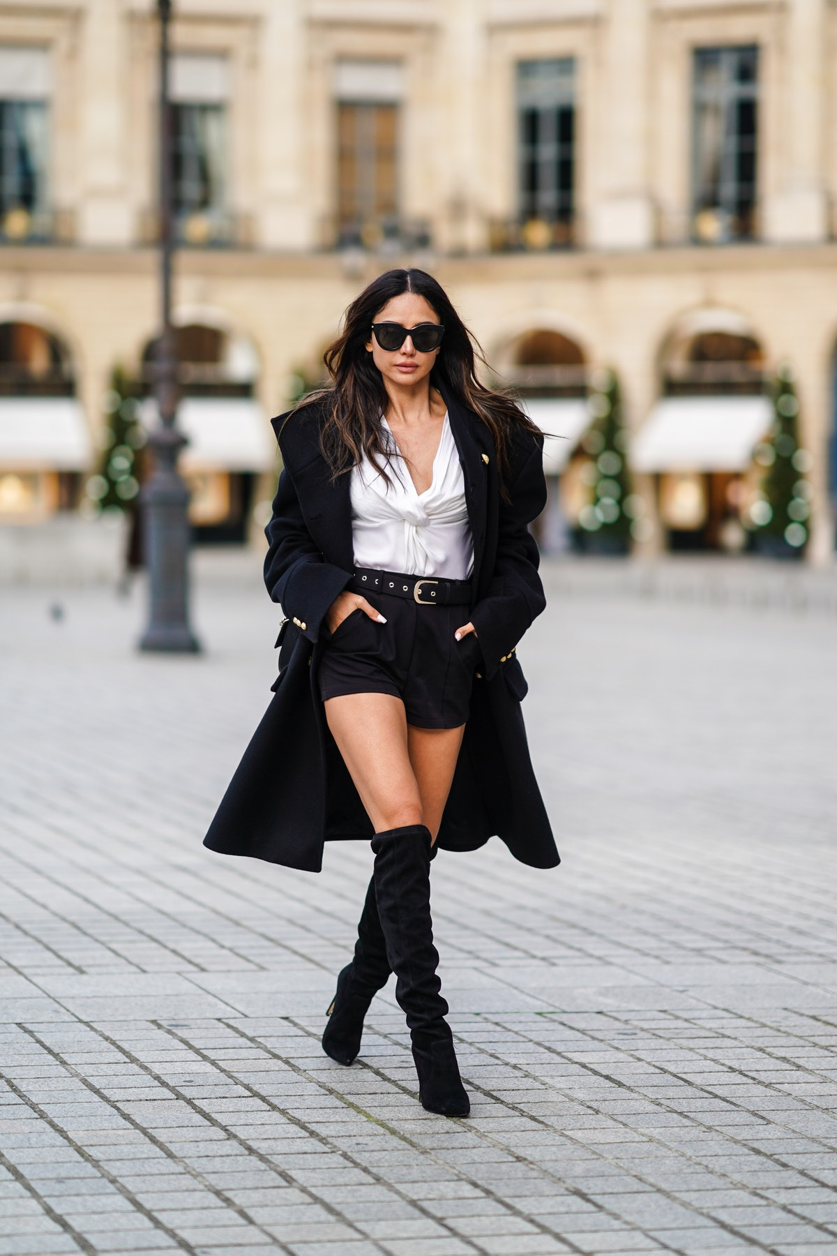 Patricia Gloria Contreras wears sunglasses from Le Specs, a black military long coat with golden but...