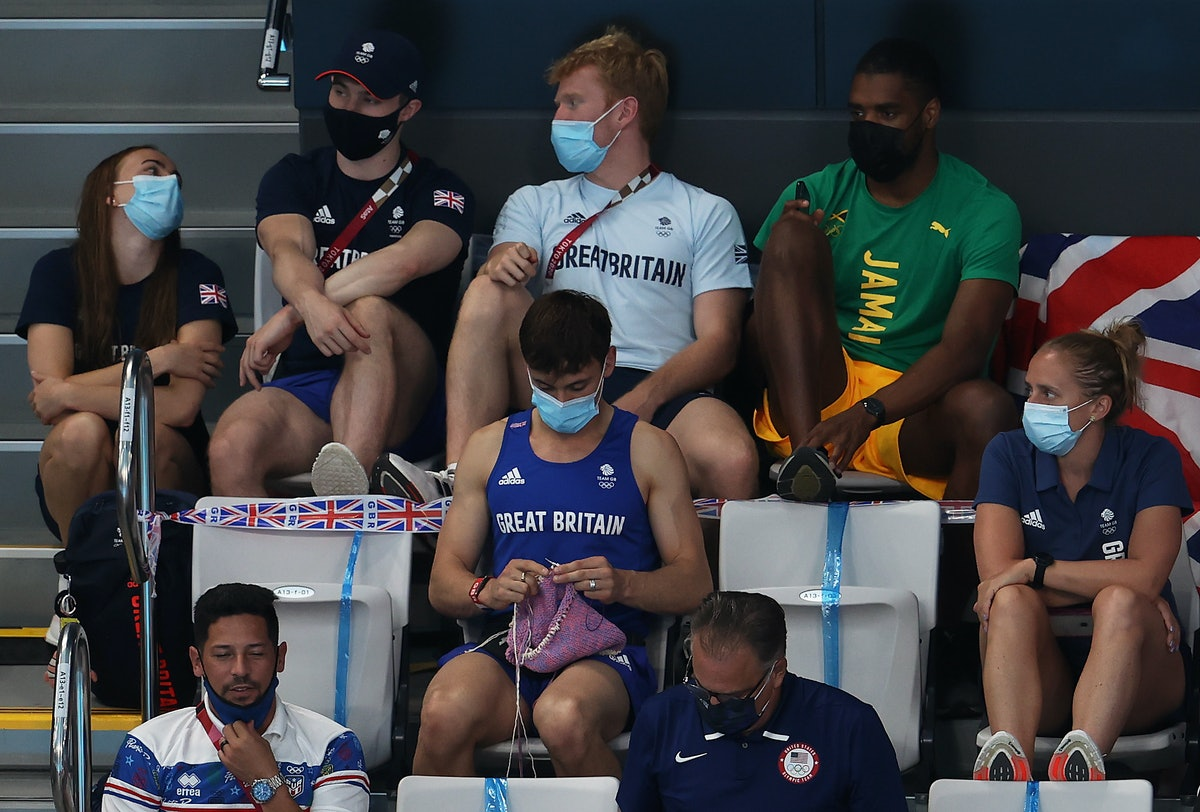 TOKYO, JAPAN - AUGUST 01: Tom Daley of Great Britain knits as he watches the Women's 3m Springboard ...