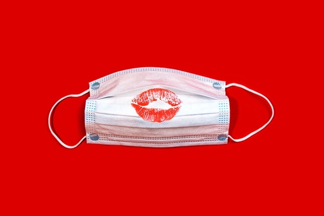 Medical mask and red lipstick kiss on red color background.  Valentine's day healthy creative concep...
