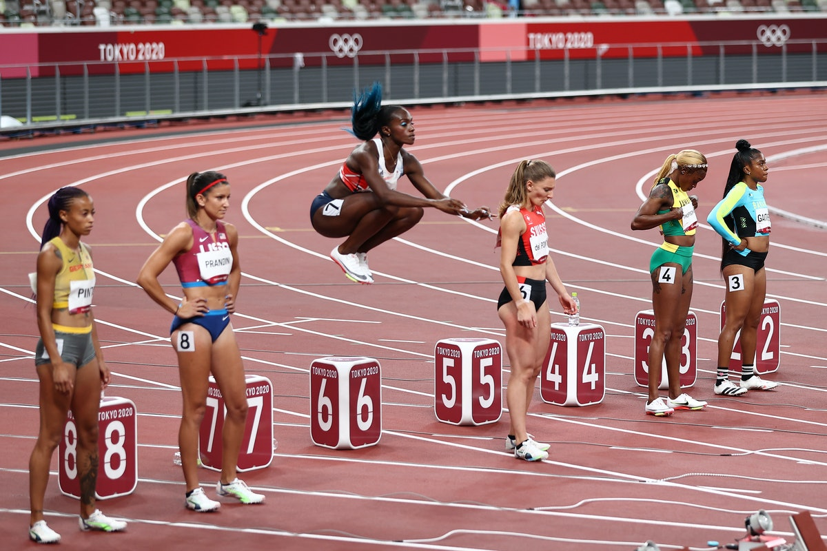 TOKYO, JAPAN - JULY 31: Dina Asher-Smith (C) of Team Great Britain warms up on the blocks during the...