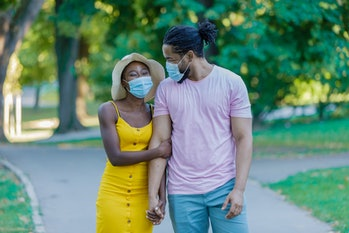 An African-American Woman and Her Lovely Husband are Walking in the Public Park with Protective Mask...