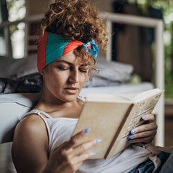 One woman sitting on the floor in bedroom at home. She is reading a book.