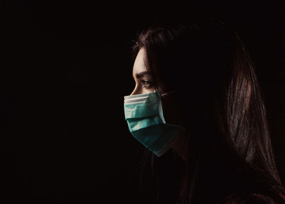 Portrait in profile of a beautiful woman in a mask on a black background