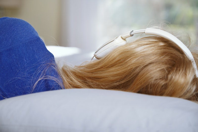 Blond woman lying on a bed and wearing headphones while listening music