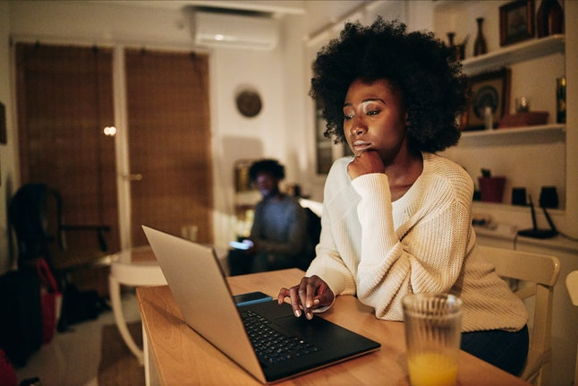 Beautiful African American woman studying in the living room on a laptop computer while living with ...