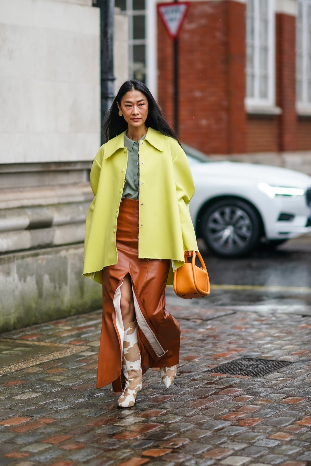 LONDON, ENGLAND - FEBRUARY 15: Fashion blogger Pornwika wears a yellow oversized jacket, an orange b...