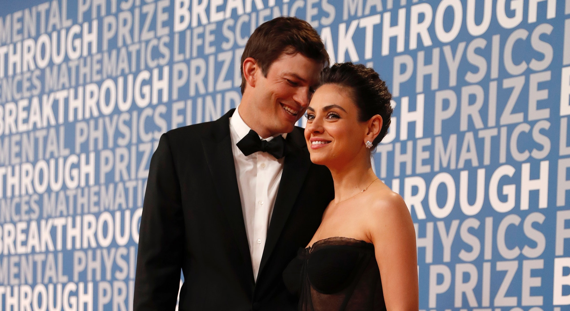 Actress Mila Kunis poses for a picture with her husband actor Ashton Kutcher on the red carpet for t...