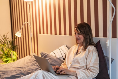 Photo of mature woman lying in bed and using laptop