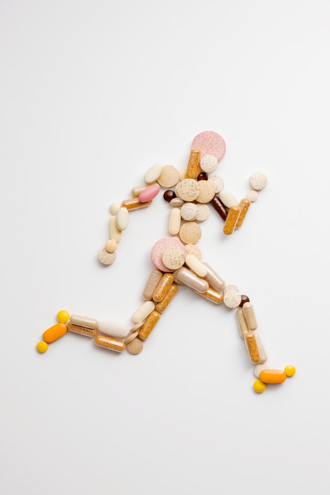 athletic runner shape made of vitamin pills viewed from above