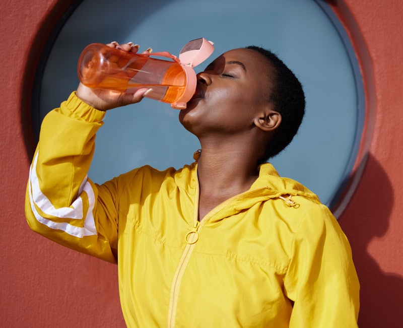 A woman drinks collagen water while wearing a yellow zip up hoodie.