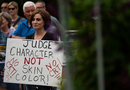 """A woman holds up a sign during a rally against """"critical race theory"""" (CRT) being taught in schools ..."""