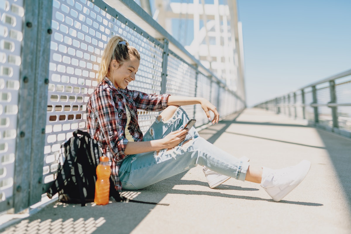 A teenager in the city with backpack looks at some POV TikTok video ideas for back-to-school videos....