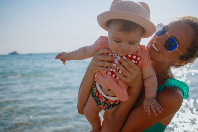Mother holding her 6 months old baby at beach. Vacation concept