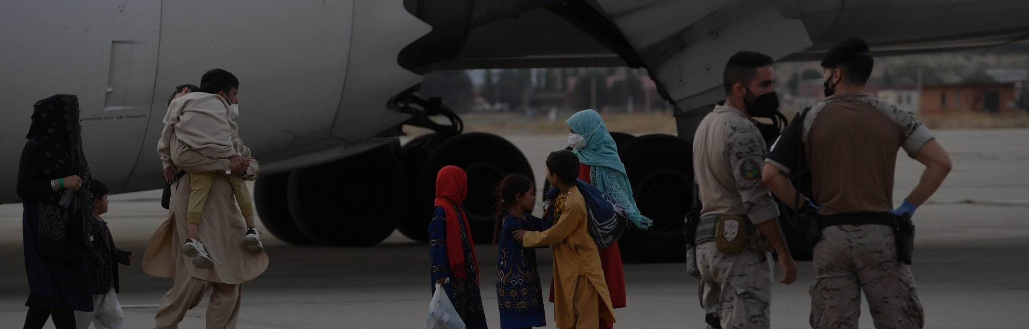 Military personnel stand on the tarmac as refugees disembark from an evacuation flight from Kabul, a...