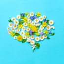 Flowers and leaves forming brain shape on blue background.