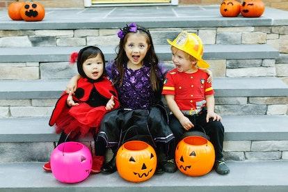 three kids in halloween costumes with pumpkin buckets