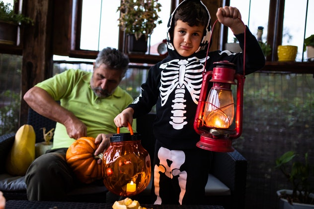 A cute boy in a skeleton costume is holding a plastic Halloween pumpkin in one hand and a metal lant...
