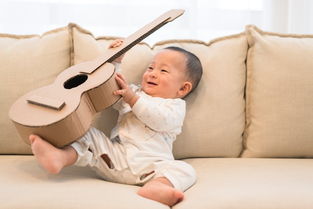 baby boy playing with guitar