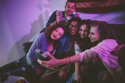 Happy multi-ethnic teenage friends taking polaroid selfies on instant photo camera at house party