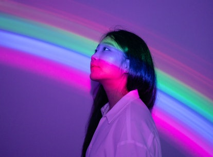 Young woman in rainbow neon lights during the September 2021 full moon in Pisces, which will affect ...