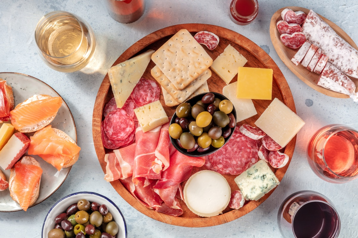 Charcuterie and cheese board with wine, overhead flat lay shot. Italian antipasti or Spanish tapas, ...
