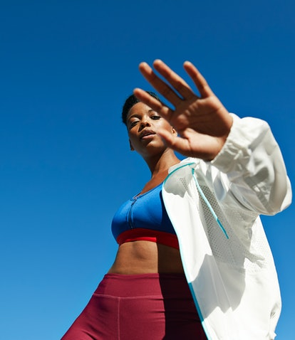 Portrait of active sportswoman wearing jacket with sports clothing against clear sky during sunny da...