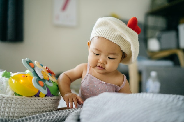 cute baby boy in hat plays with toys