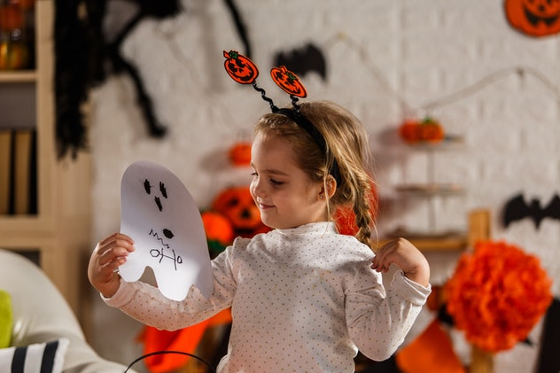 Front view of adorable little girl holding a ghost mask that she is gonna wear as a part of her cost...