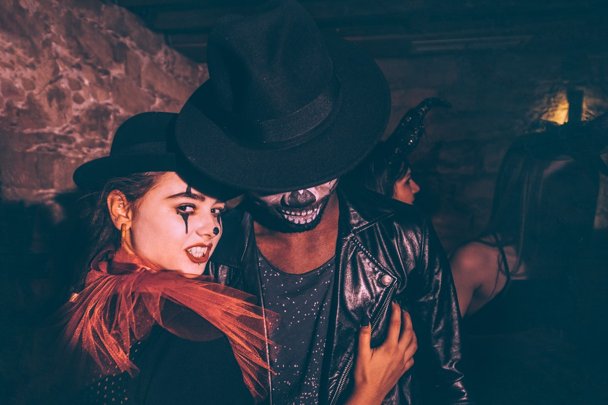 Young multi-ethnic couple in Halloween costumes and scary make-up having fun at night party