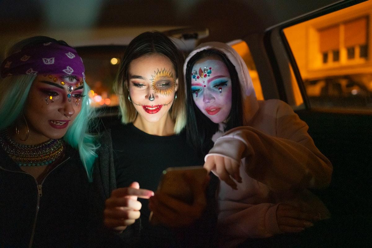 Women help a friend compose a sexy Halloween text.