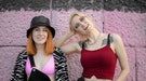 two women smiling at the camera in front of a pink wall, discussing aries libra friendship compatibi...