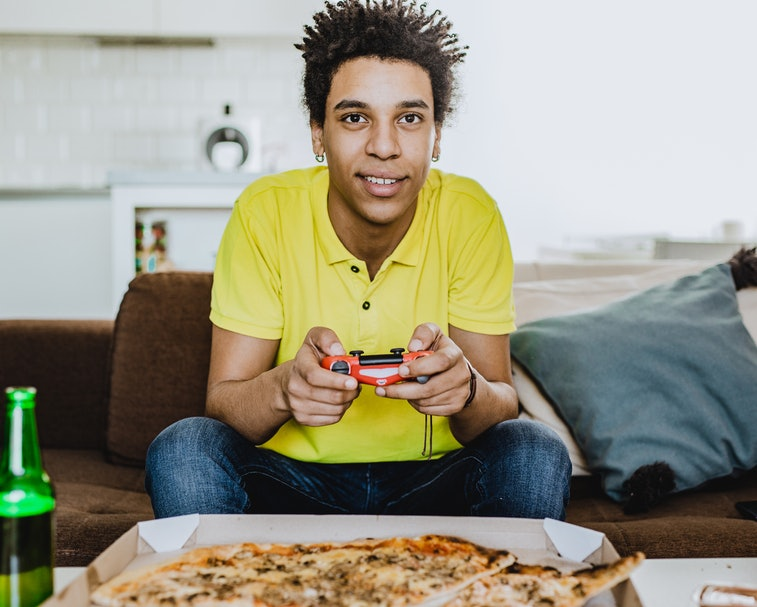 Young African American man eating pizza, drinking beer and playing video games
