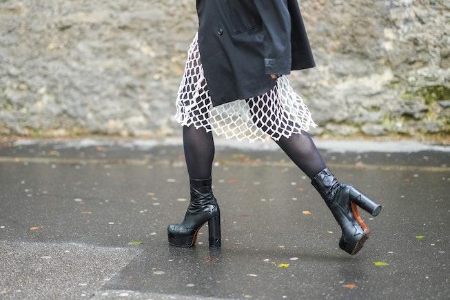 PARIS, FRANCE - JULY 04: A guest wears a black oversized blazer jacket, black tights, a white mesh k...