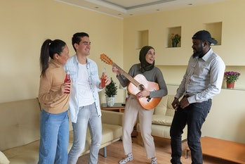 Friends are Excited While Listening to Their Female Muslim Friend with Hijab Who is Playing an Acous...