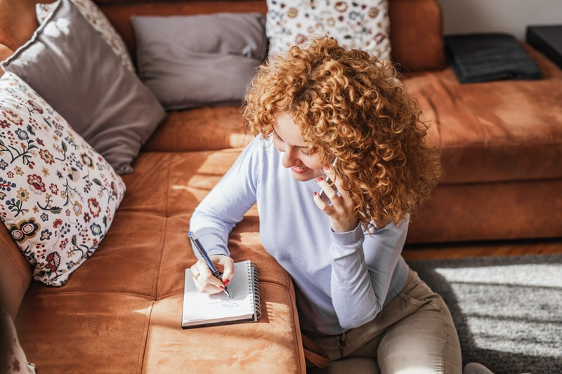 Young woman talking on the phone at home and writing notes in living room