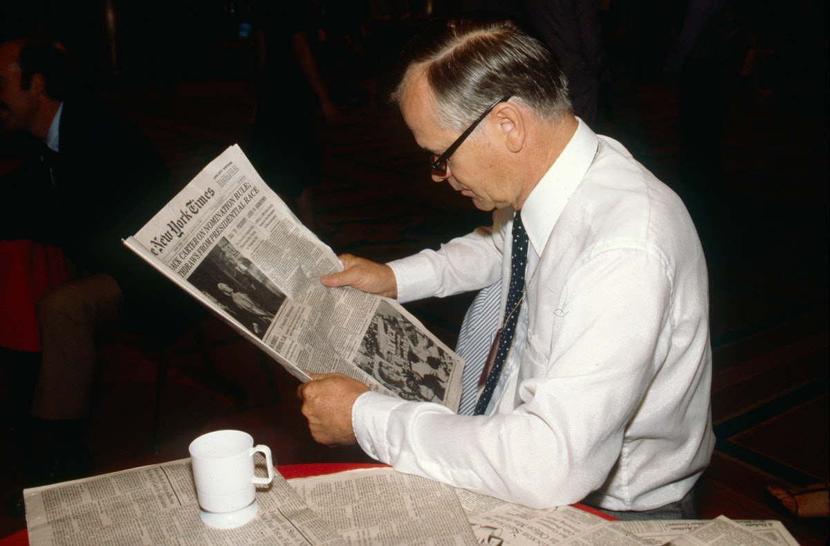 View of an unidentified man as he reads a copy of the New York Times, New York, New York, August 14,...