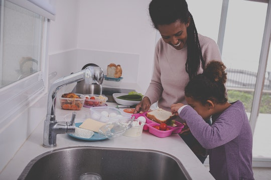 A young mother and her 6 years old girl preparing breakfast and lunch for school and work. Curious l...