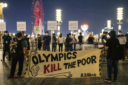 TOKYO, JAPAN - JULY 29: People hold placards during an anti-Olympics protest in front of Tokyo 2020 ...