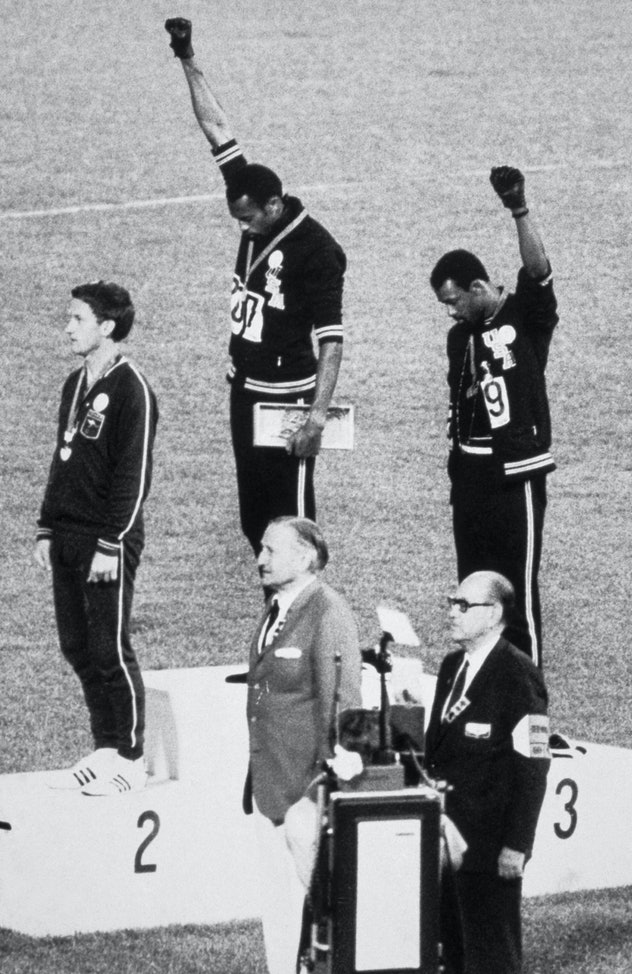 American sprinters Tommie Smith and John Carlos raise their fists and give the Black Power Salute at...