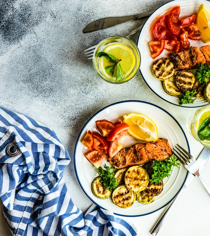 overhead image of two plates full of zucchini, tomato, and salmon