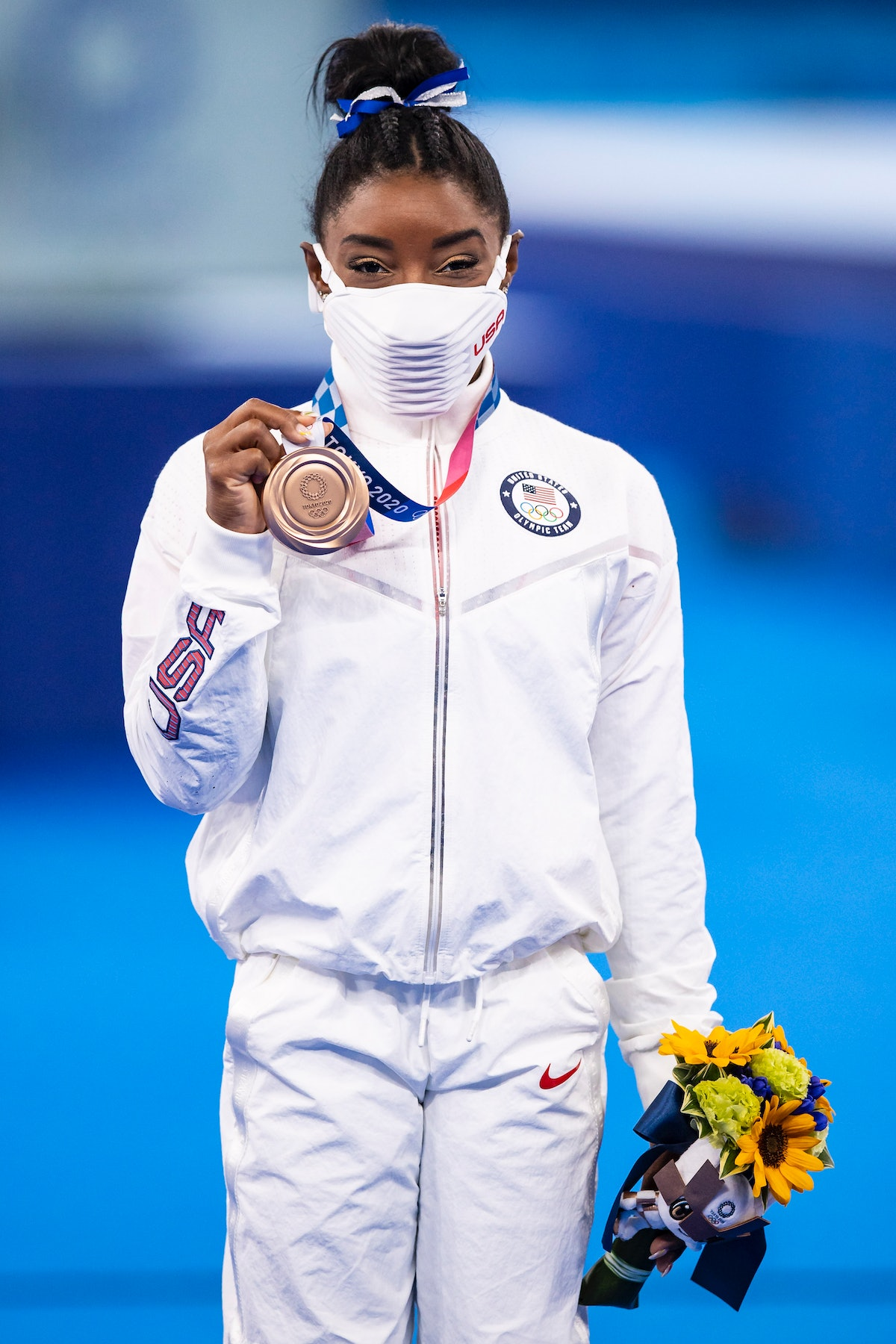 Simone Biles, wearing an all-white Team USA tracksuit, shows off her bronze medal at the 2021 Olympi...