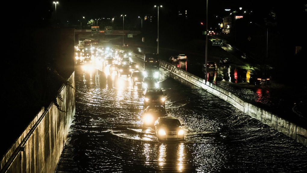 DETROIT, MICHIGAN, UNITED STATES - 2021/07/24: Vehicles cautiously drive through floodwaters on I-94...