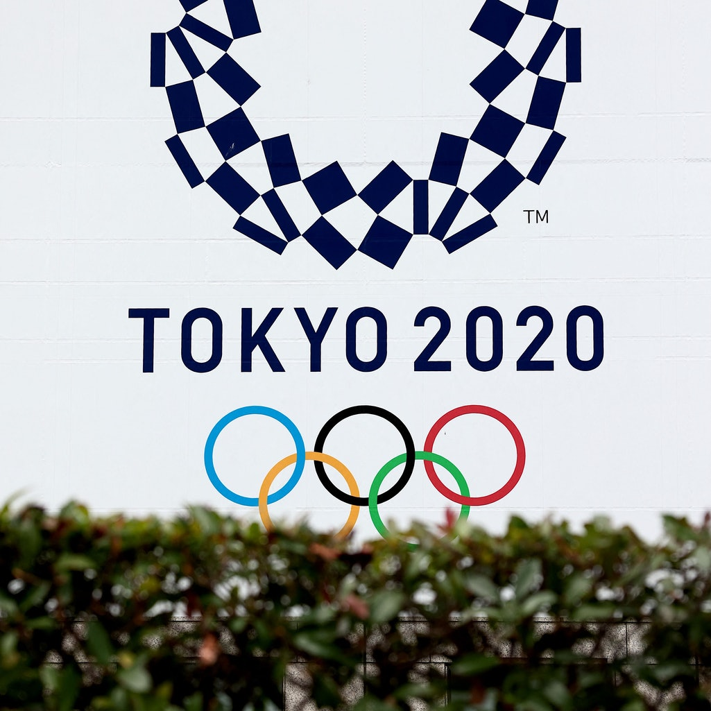 The Tokyo Olympic Games logo is visible over foliage in Japan.