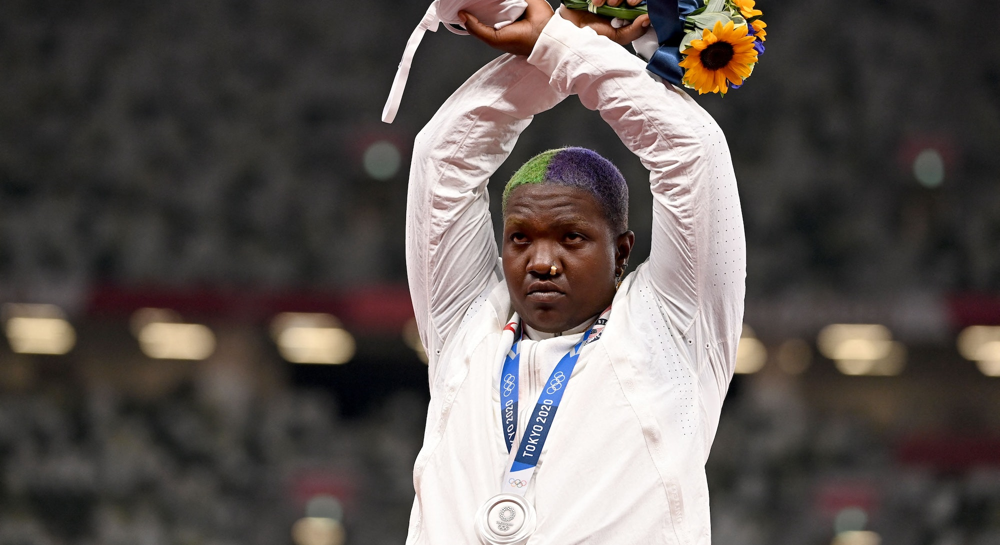 Raven Saunders makes an 'X' with her wrists on the podium of the women's shot put event after receiv...