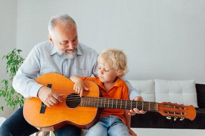 Happy grandpa teaching his grandson to play guitar.