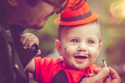 Father with his cute baby boy dressed as pumpkin at Halloween